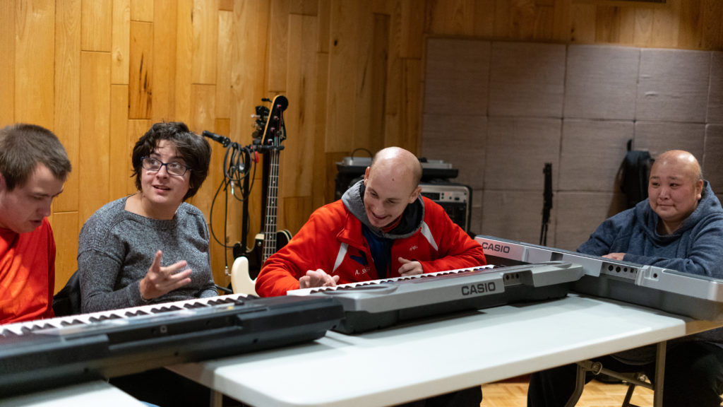 Disabled adults participating in music therapy class and playing piano.